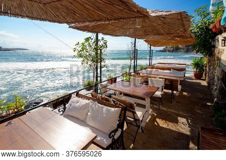 Empty Terrace Of A Restaurant On The Sea. Beautiful View In To The Bay In Morning Light. Decorative