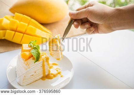 Close Up Mango Crepe Cake Sliced On A White Plate With A Woman Hand Holding A Spoon With A Piece Of