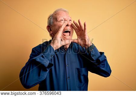 Grey haired senior man wearing casual blue shirt standing over yellow background Shouting angry out loud with hands over mouth