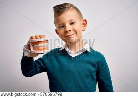 Young little caucasian kid holding dental prosthesis teeth denture over isolated background with a happy face standing and smiling with a confident smile showing teeth