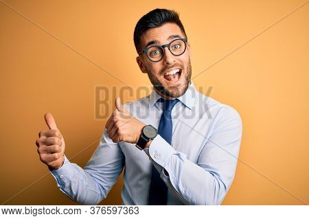Young handsome businessman wearing tie and glasses standing over yellow background Pointing to the back behind with hand and thumbs up, smiling confident