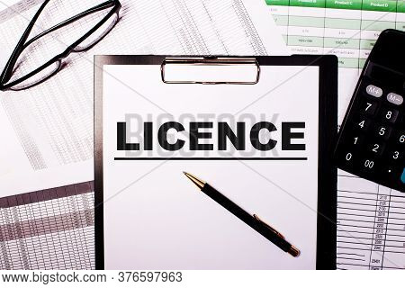 The Word Licence Is Written In A White Notebook Next To Glasses And A Calculator. Business Concept