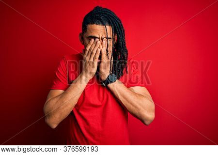 Young handsome african american afro man with dreadlocks wearing red casual t-shirt rubbing eyes for fatigue and headache, sleepy and tired expression. Vision problem