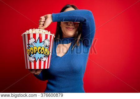 Young blonde woman wearing 3d glasses and eating pack of popcorn watching a movie on cinema Smiling cheerful playing peek a boo with hands showing face. Surprised and exited
