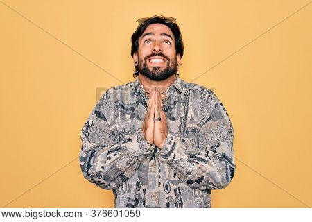 Young handsome hispanic bohemian man wearing hippie style and sunglasses begging and praying with hands together with hope expression on face very emotional and worried. Begging.