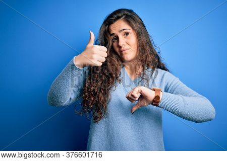 Young beautiful woman with curly hair wearing blue casual sweater over isolated background Doing thumbs up and down, disagreement and agreement expression. Crazy conflict