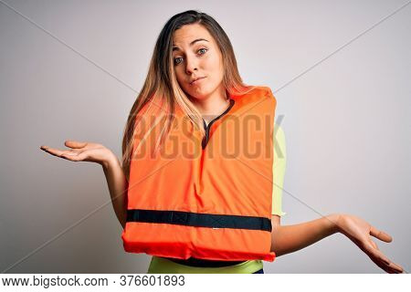 Young beautiful blonde woman with blue eyes wearing orange lifejacket over white background clueless and confused expression with arms and hands raised. Doubt concept.