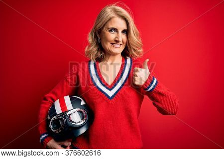 Middle age beautiful blonde motorcyclist woman holding moto helmet over red background happy with big smile doing ok sign, thumb up with fingers, excellent sign