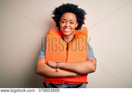 Young African American afro woman with curly hair wearing orange protection lifejacket happy face smiling with crossed arms looking at the camera. Positive person.