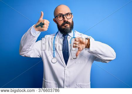 Handsome bald doctor man with beard wearing glasses and stethoscope over blue background Doing thumbs up and down, disagreement and agreement expression. Crazy conflict