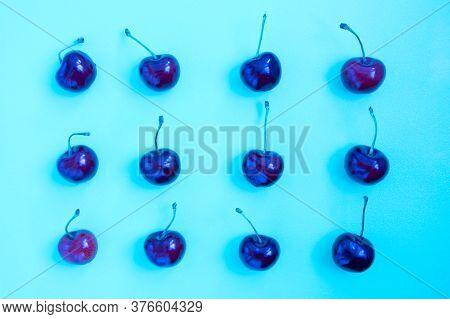 Neon Bright Blue Cherry On A Ultraviolet Background. Cherry Pattern. Cherries Closeup. Summer Flat L