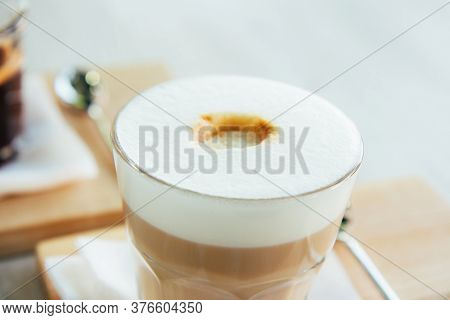 Latte Or Cappuccino In A Glass Cup On A Wooden Tray. Morning Coffee With Foam On A Wooden Table. Clo