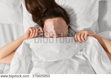 people, bedtime and rest concept - woman with eye sleeping mask lying in bed under blanket