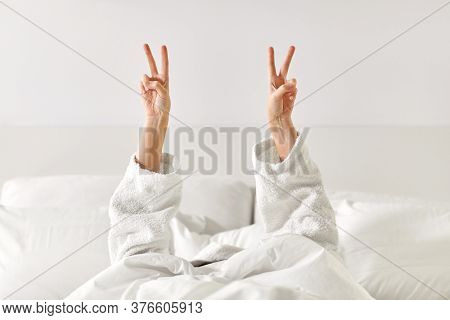 gesture, comfort and morning concept - hands of young woman in hotel robe lying in bed and showing peace hand sign at bedroom