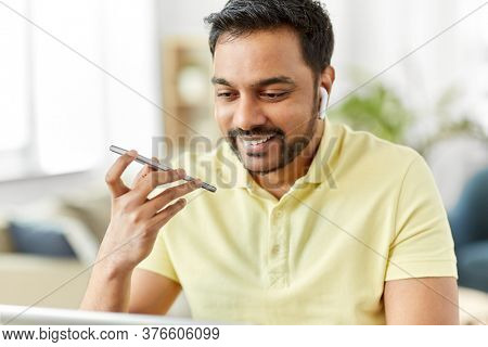 technology, communication and people concept - close up of happy smiling indian with smartphone, earphones and laptop computer using voice command recorder at home office
