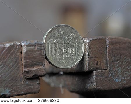 Coin 10 Turkish Bin Lira Clamped In A Vise. The Concept Of Financial And Economic Problems.