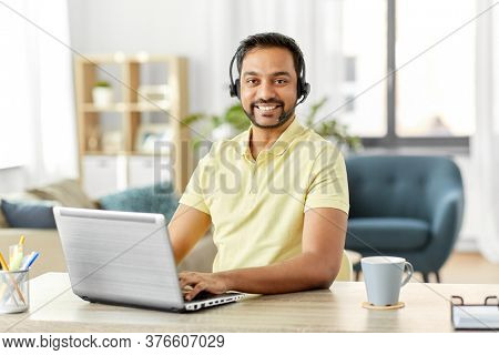 remote job, technology and people concept - happy smiling indian man with headset and laptop computer having conference call at home office