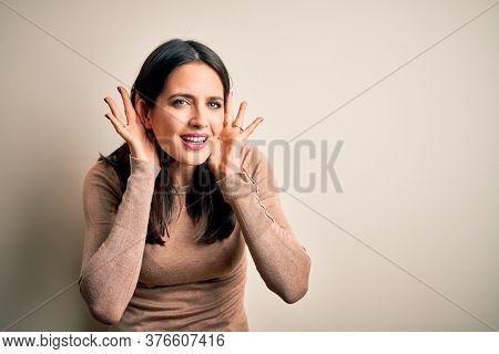 Young brunette woman with blue eyes wearing casual sweater over isolated white background Trying to hear both hands on ear gesture, curious for gossip. Hearing problem, deaf
