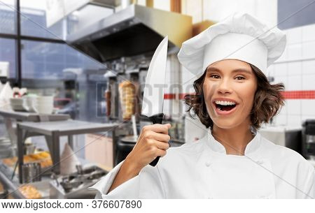 cooking, culinary and people concept - happy smiling female chef in toque with knife over restaurant or kebab shop kitchen background