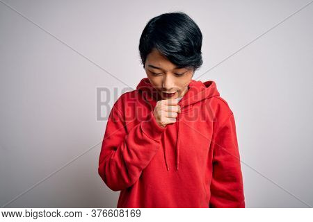 Young beautiful asian girl wearing casual sweatshirt with hoodie over white background feeling unwell and coughing as symptom for cold or bronchitis. Health care concept.