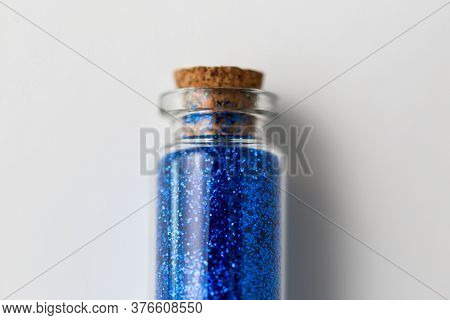 party, decoration and holidays concept - close up of ultramarine blue glitters in small glass bottle with cork stopper over white background