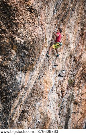 A Strong Man Climbs A Cliff. Climber Overcomes A Difficult Climbing Route On A Natural Terrain. Rock