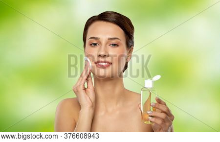 beauty, skin care and people concept - smiling young woman with toner or cleanser and cotton pad cleansing face over lime green natural background