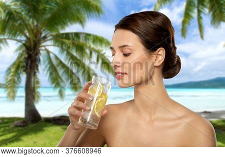 beauty and detox concept - woman drinking fresh water with lemon and ice over tropical beach background in french polynesia