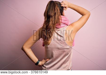 Young beautiful brunette sportswoman wearing sportswear and towel over pink background Backwards thinking about doubt with hand on head