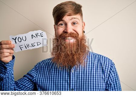Redhead Irish business man with beard holding paper with you are fired text with a happy face standing and smiling with a confident smile showing teeth