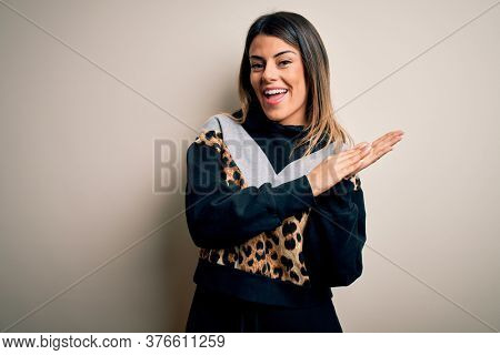 Young beautiful woman wearing casual sweatshirt standing over isolated white background clapping and applauding happy and joyful, smiling proud hands together