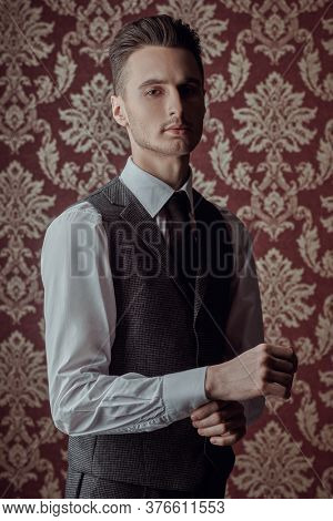 Portrait of a handsome man in elegant classic suit and a tie on a vintage background. Business style. Men's fashion.