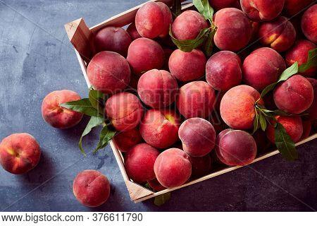 Organic ripe peaches in wooden crate