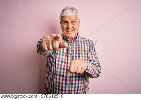 Senior handsome hoary man wearing casual colorful shirt over isolated pink background pointing to you and the camera with fingers, smiling positive and cheerful