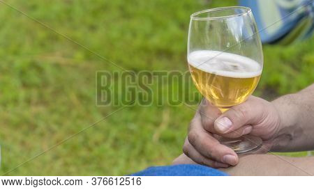 Mans Hand Take Apple Cider In A Glass. Camping.