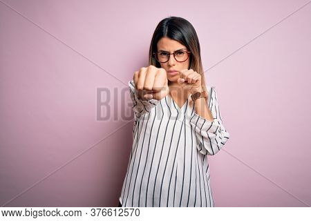 Young beautiful woman wearing casual striped t-shirt and glasses over pink background Punching fist to fight, aggressive and angry attack, threat and violence
