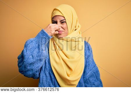 Young beautiful brunette muslim woman wearing arab hijab over isolated yellow background smelling something stinky and disgusting, intolerable smell, holding breath with fingers on nose. Bad smell