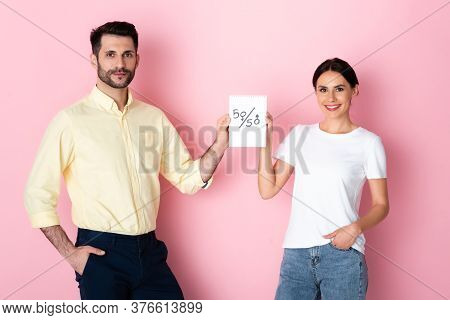 Happy Man And Woman In White T-shirt Holding Paper With Fifty-fifty Symbols While Standing With Hand