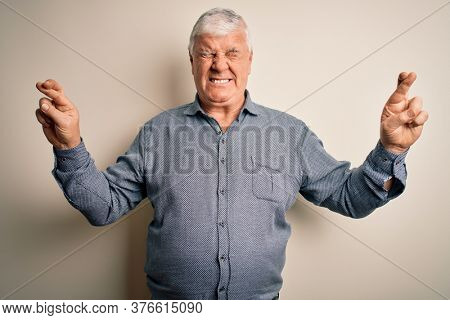 Senior handsome hoary man wearing casual shirt standing over isolated white background gesturing finger crossed smiling with hope and eyes closed. Luck and superstitious concept.