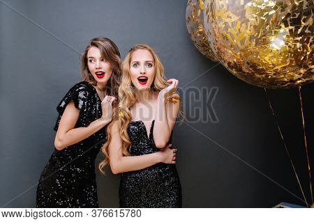 Happy Party Of Two Fashionable Amazing Young Women On Black Background. Luxury Black Dress, Long Cur