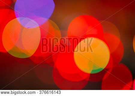 Abstract Blurred Bokeh Boke Background Of Dot Lights Through Branches In Evening Park. Red And Yello