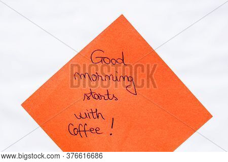 Good Morning Starts With Coffee Handwriting Text Close Up Isolated On Orange Paper With Copy Space.