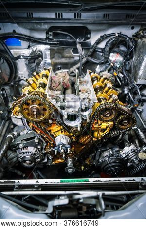 Car Repair: Type Of Open Engine With Drive Chains And A Large Number Of Pulleys And Parts.