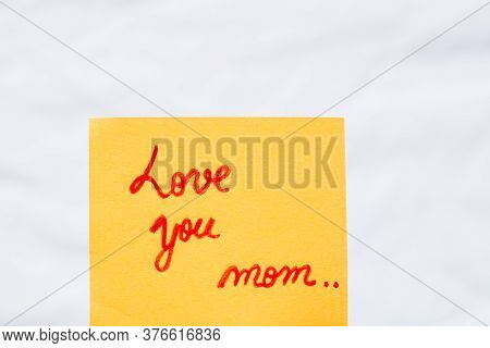 Love You Mom Handwriting Text Close Up Isolated On Orange Paper With Copy Space. Writing Text On Mem