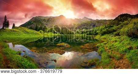 Dramatic Sunrise At A Lake In The Alps With Mountains, Red Clouds Reflected In The Clear Water And P