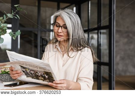 Photo of mature serious concentrated woman indoors at home reading newspaper