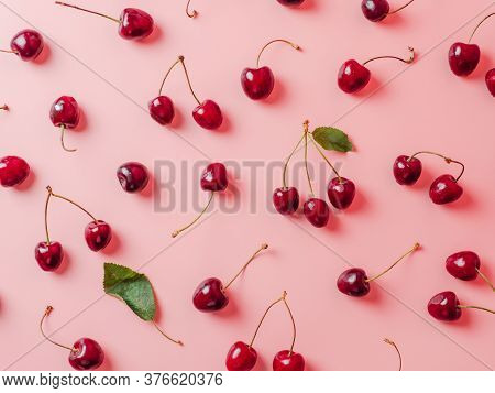 Fresh Cherries Scattered On Pink Background. Creative Fresh Cherry Pattern Background With Copy Spac