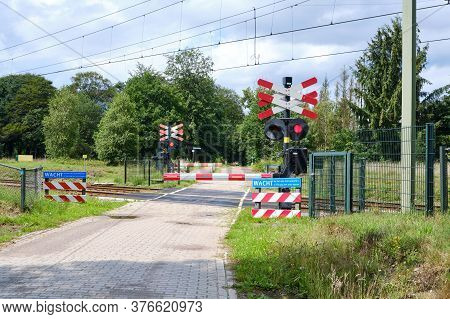 Railway Crossing With Closed Barriers And Blinking Red Lights. Blue Warning Sign Dutch Text, Wait Ti
