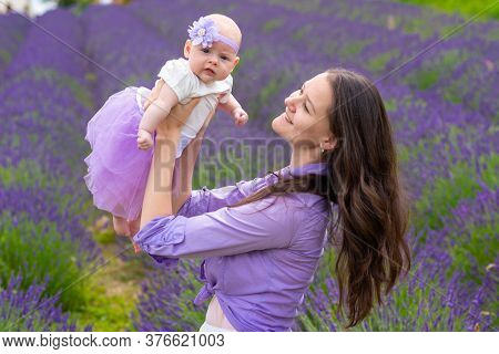 Mother Walks With Her Little Daugher Holding A Bouquet Of Lavander In Czech Republic