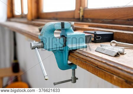 A Vise Is Attached To The Edge Of The Window Sill. Metal Tool.